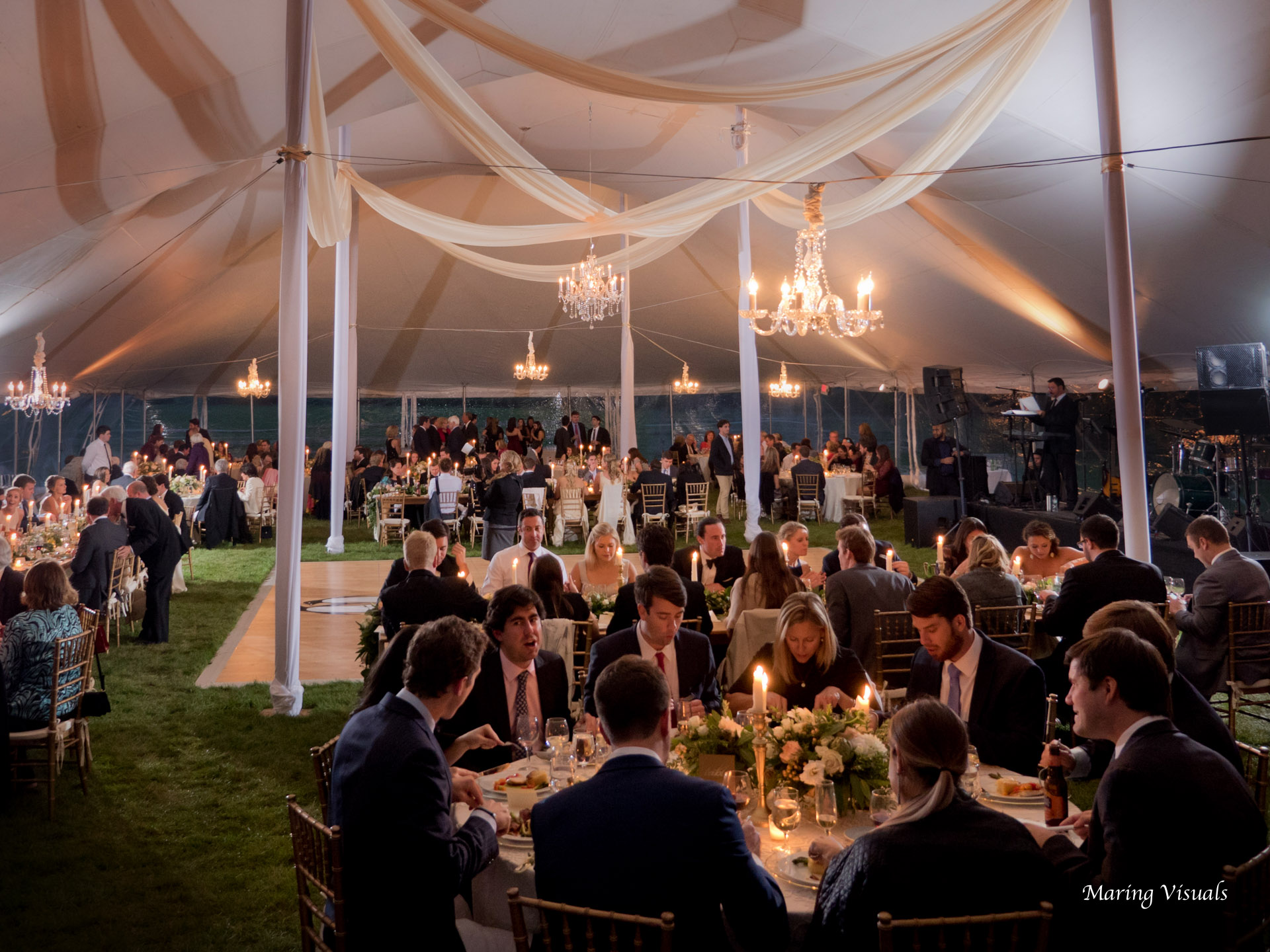 A mixture of round and long tables accented by chandeliers and candlelight have the tent a heartwarming atmosphere