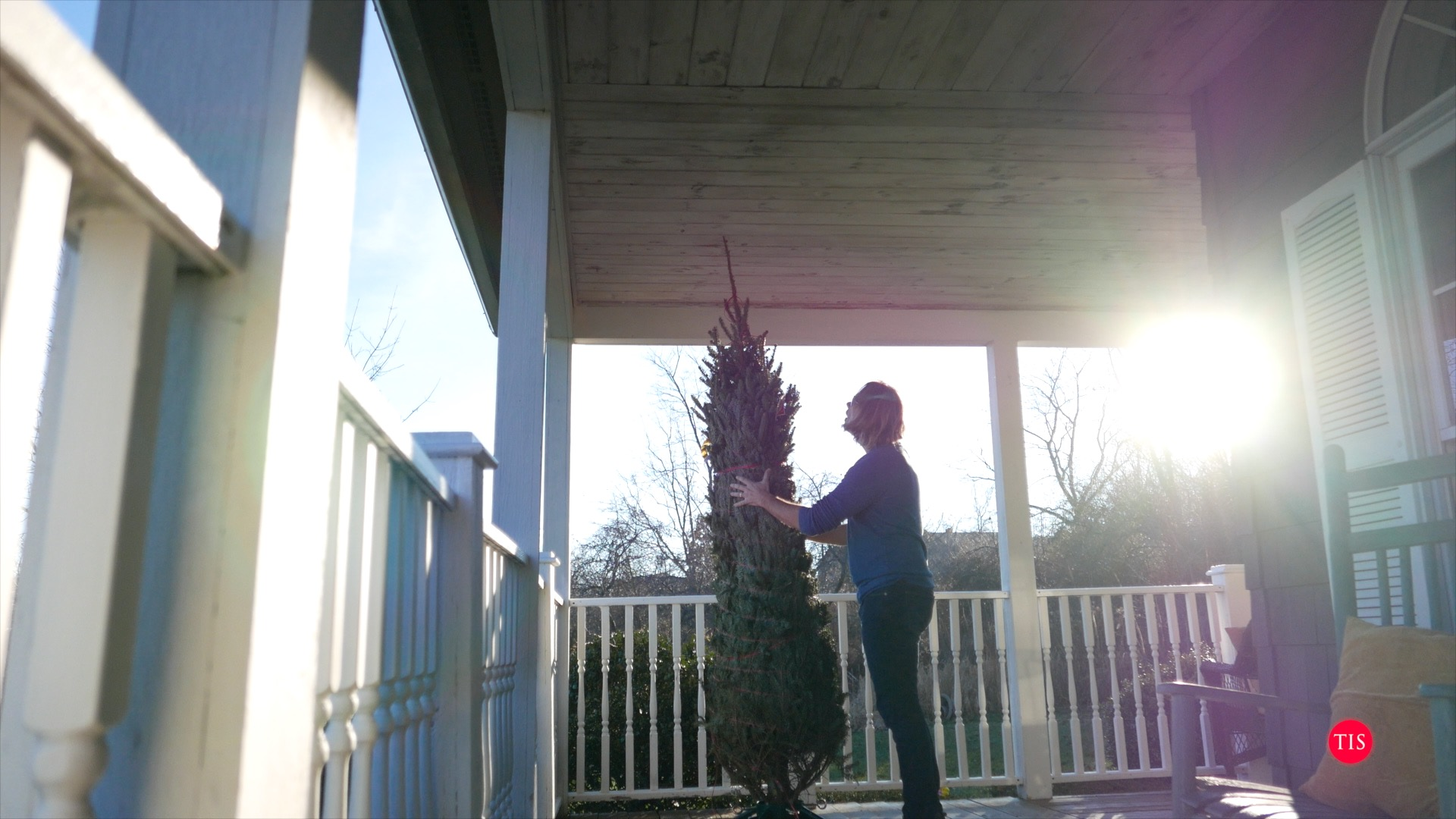 Charles Maring putting a fresh tree on the front porch of the Connecticut home.