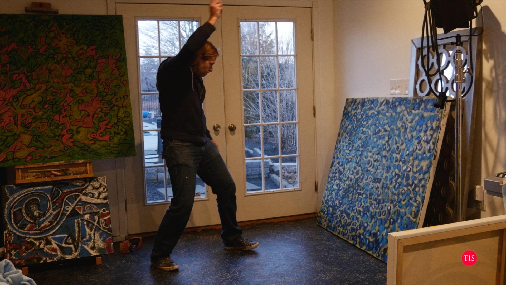 Charles dancing to reggae music while painting.
