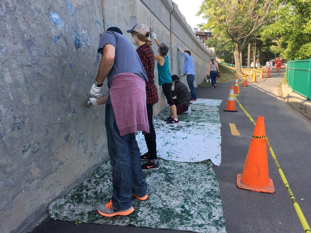 Volunteers from Boston Cares help prep concrete walls for painting.