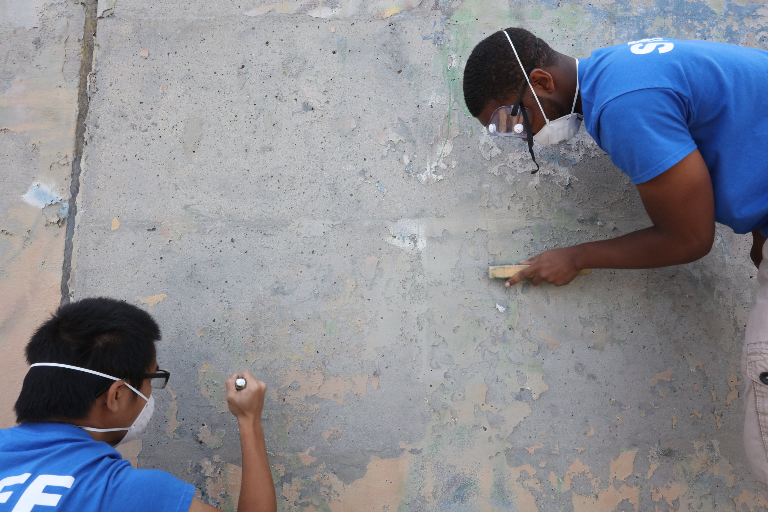 Volunteers from the Espanade Association help scrape the wall before painting on  Patterned Behavior.