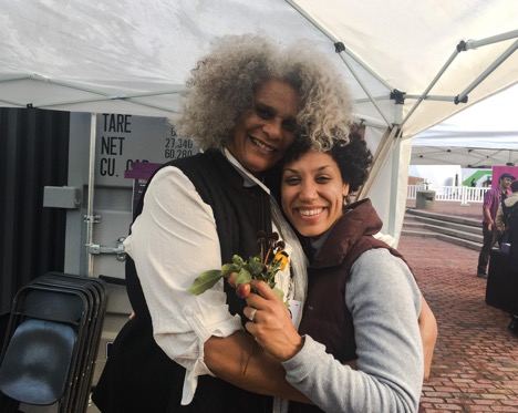 Lolita Parker, Jr. and Elisa Hamilton embrace after a slide talk; Elisa clutches garden seeds gifted to her by Lolita.  Photo courtesy of the artist.