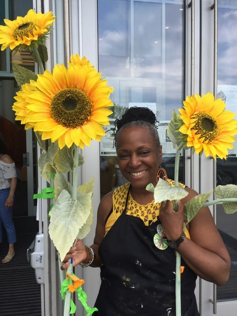 Ekua Holmes with sunflowers grown & harvested as part of  The Roxbury Sunflower Project