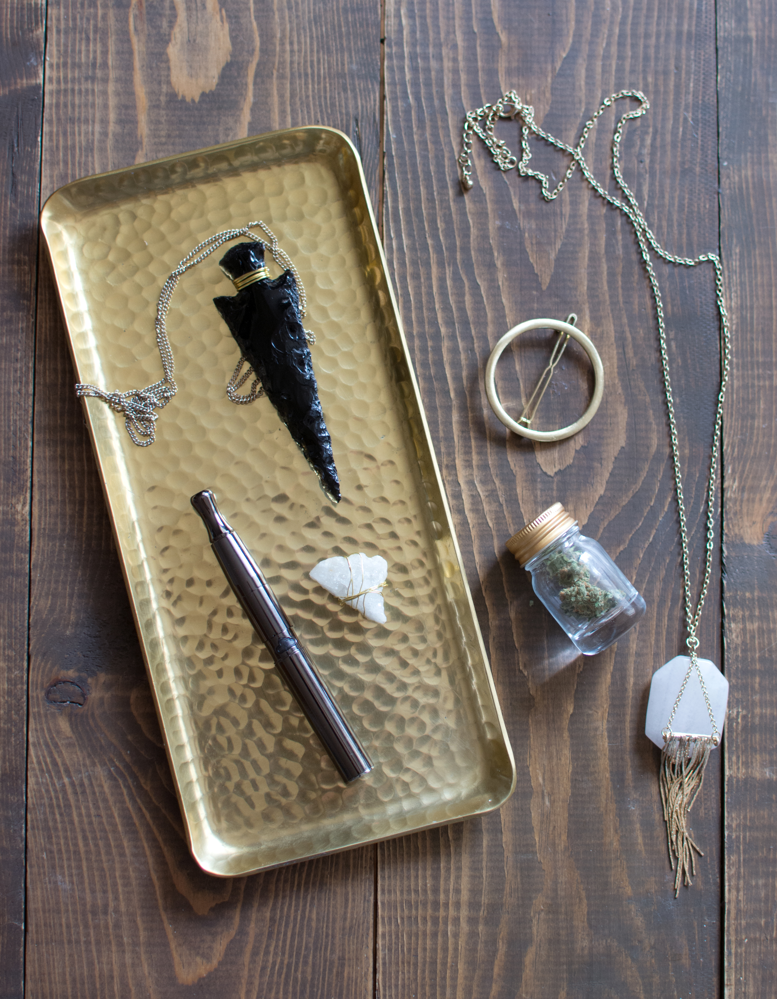 Gold tray from Hobby Lobby  / Puffco reloadable concentrate vape pen  /Obsidian arrow head from crystal shop in Sedona / Quartz crystal from Earthbound  / Gold circle hair clip from Francescas  /  Quartz + Gold crystal necklace from Francescas  /  Miniature gold-lidded jar from Michael's  /  Durban Berry bud from The Farm Co.