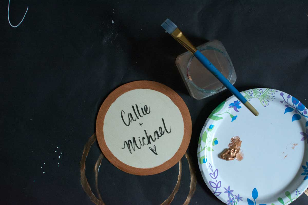 A little plywood circle bought at Hobby Lobby, painted the rim copper (the color of the roof of the barn they'll be getting married in), then brush-lettered their names to go in the center of the wreath on the door