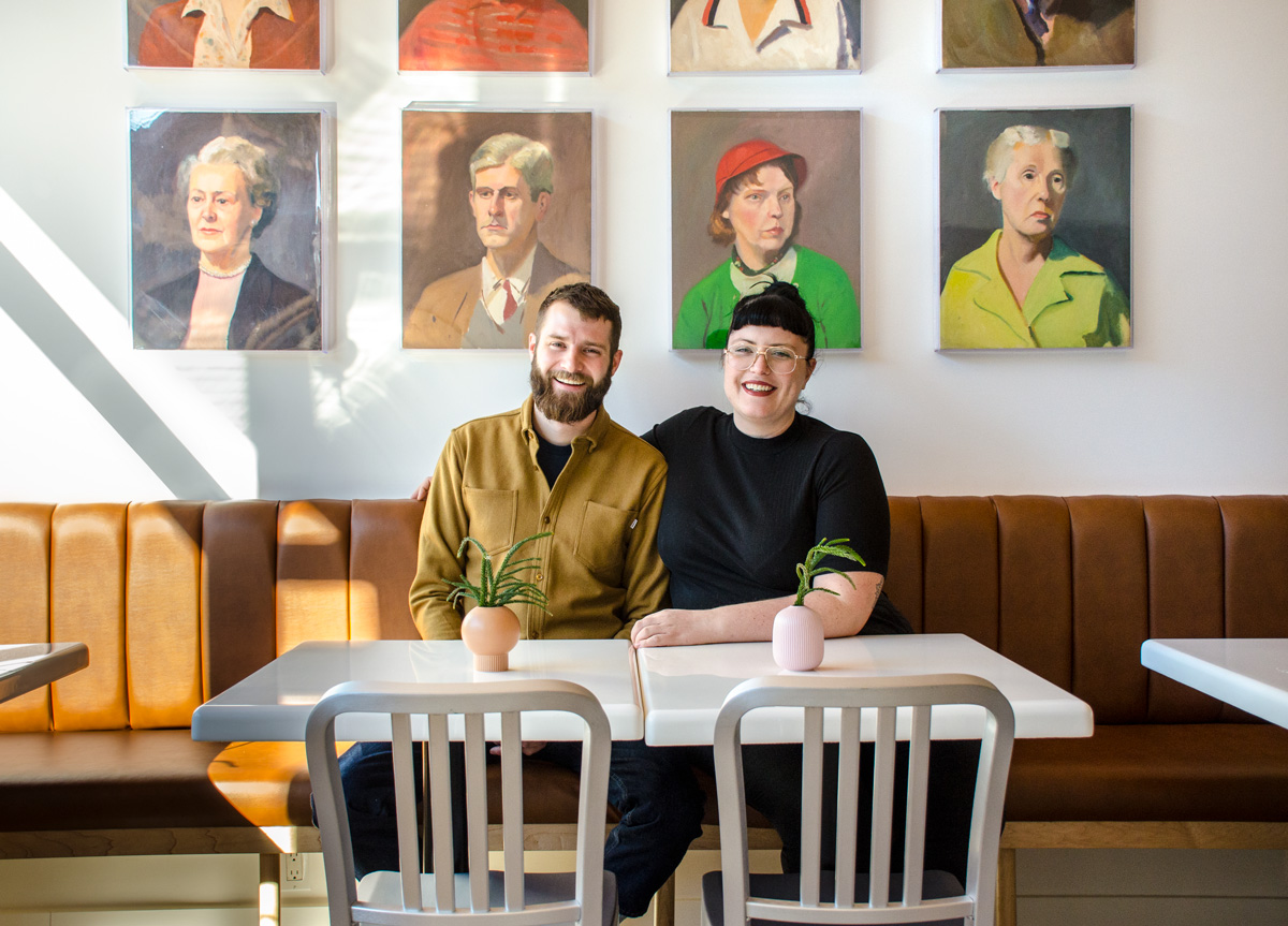 Bill Clark and Libby Willis, seated at their restaurant MeMe's Diner in Prospect Heights, Brooklyn, in front of paintings by Libby's grandfather.