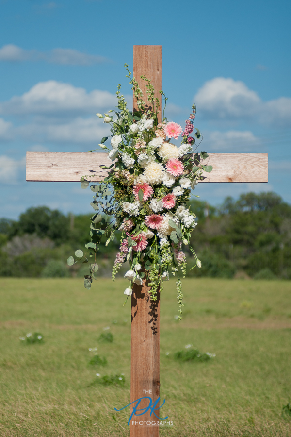 A cross with flowers was set up right behind Rachel and Nelson during their wedding ceremony.