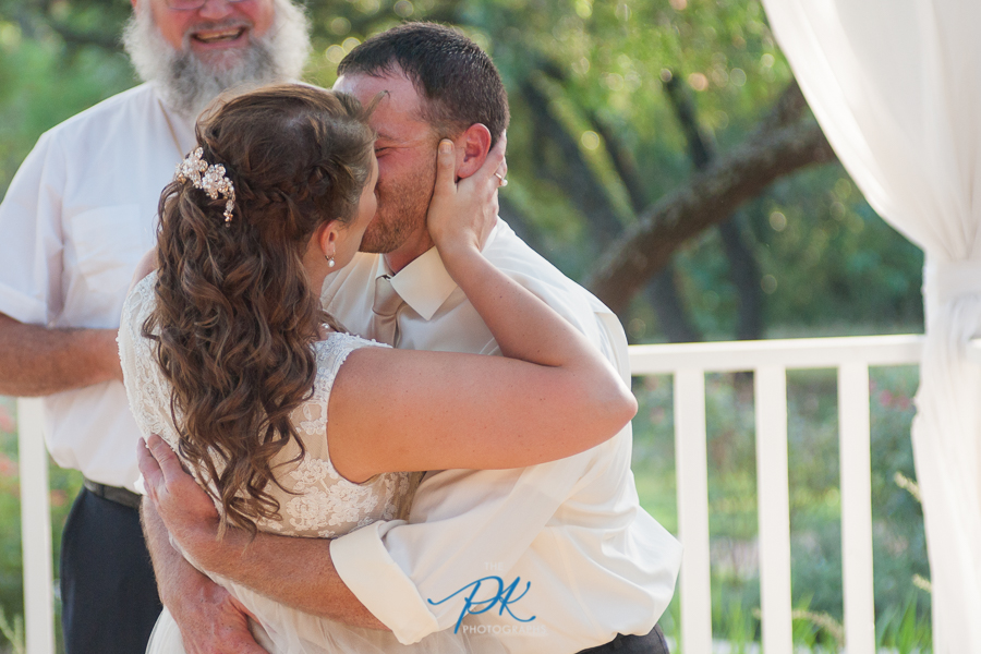 Denise and Brian's kiss at their wedding ceremony at Gardens at Old Town Helotes.