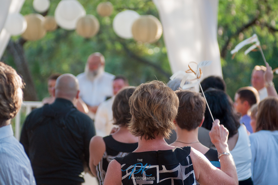 All the guests gathered around during their first kiss at the end of their wedding ceremony.