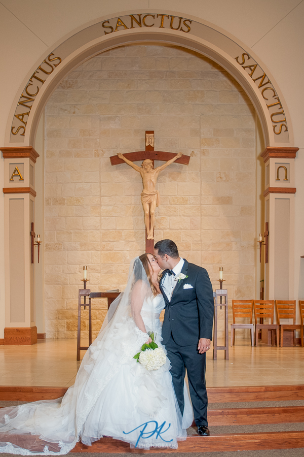 bride-groom-st-joseph-honey-creek-catholic-church-wedding-ceremony-kiss.jpg