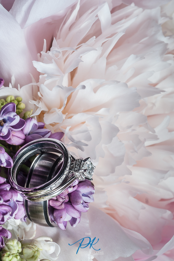 """The brides bouquet usually provides a whole host of options when it comes to ring shots. Depending on the type of flowers, you may decide to nestle the rings inside a flower, on leaves, or place them on or around part of the bouquet.It is imperative to be extra careful to not crush any of the delicate flowers. This image was shot at f/13 with a 100mm lens and 1:1 macro adapter, shutter speed of 1/250th, and ISO 100. Typically I wouldn't shoot rings at f/13, but the macro adapter completely changes the game when it comes to depth of field, and the lighter colored flowers """"in the background"""" are simple and non-distracting, so there is no reason to throw them out of focus."""