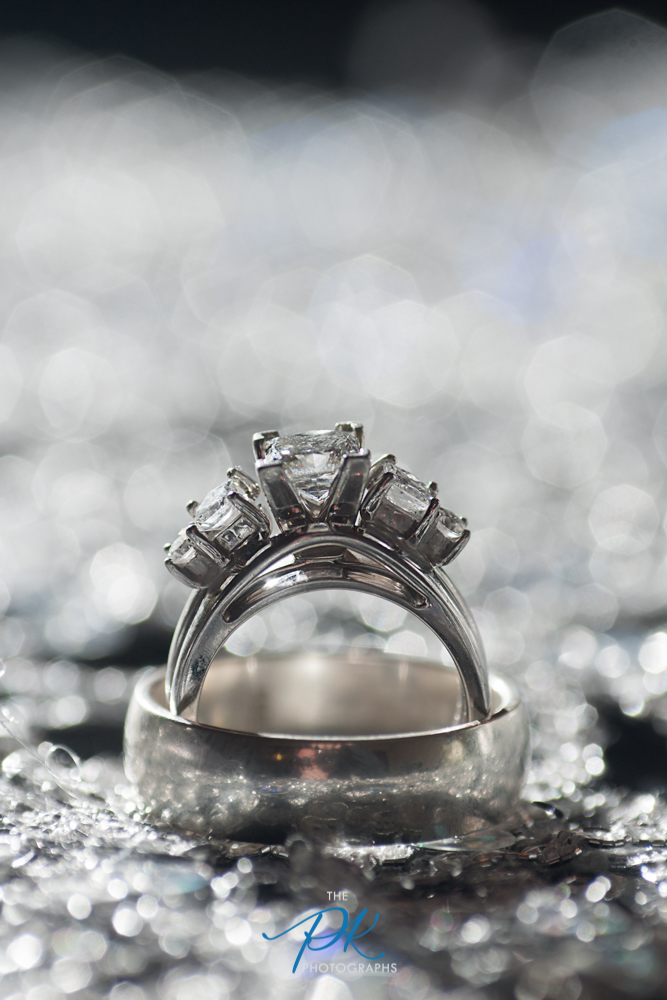 This couple had a silver sequined table runner over their guest book table. During dinner, I slipped out and set up their rings on the table, and using my tripod snapped this image. Shot at f/6.3, shutter speed 1/100th, ISO 200, with my 100mm lens and 1:1 macro adapter, back-lit with off camera flash. I was really pushing it with the aperture below f/8 while using a macro adapter, but I love the image.