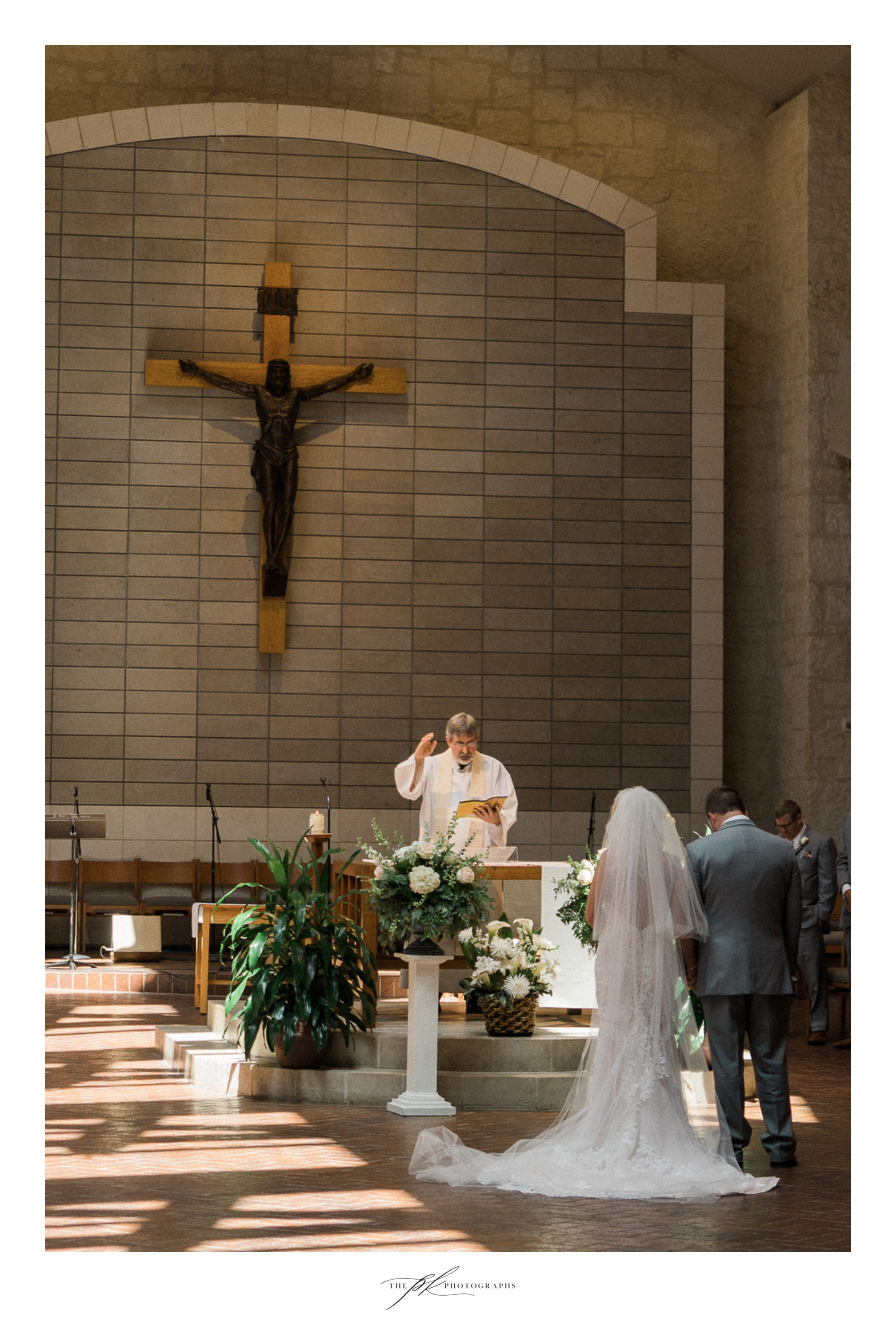 Courtney and Shane were blessed by the priest at the alter during their wedding cermeony.  St. Peter the Apostle Catholic Church | San Antonio Wedding Photographer