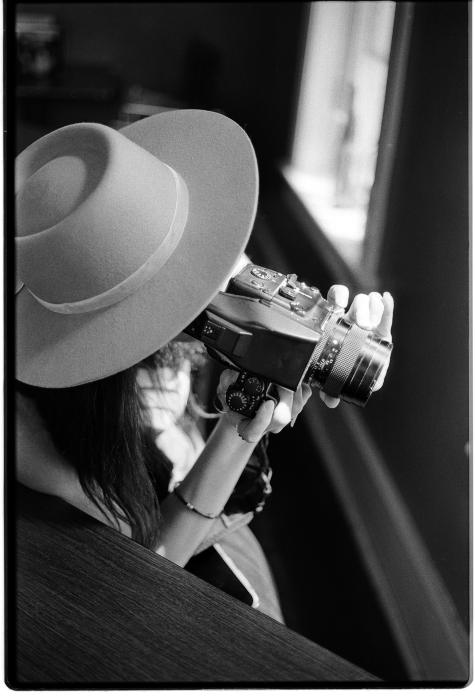 May photographing bottles on a window ledge with her medium format film camera.  Captured, developed and scanned by Parker on  Ilford HP5+  | 35mm