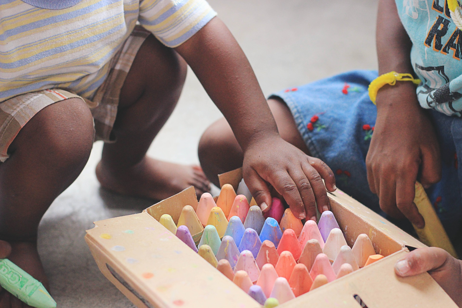 Two young children playing with a big box of chalk