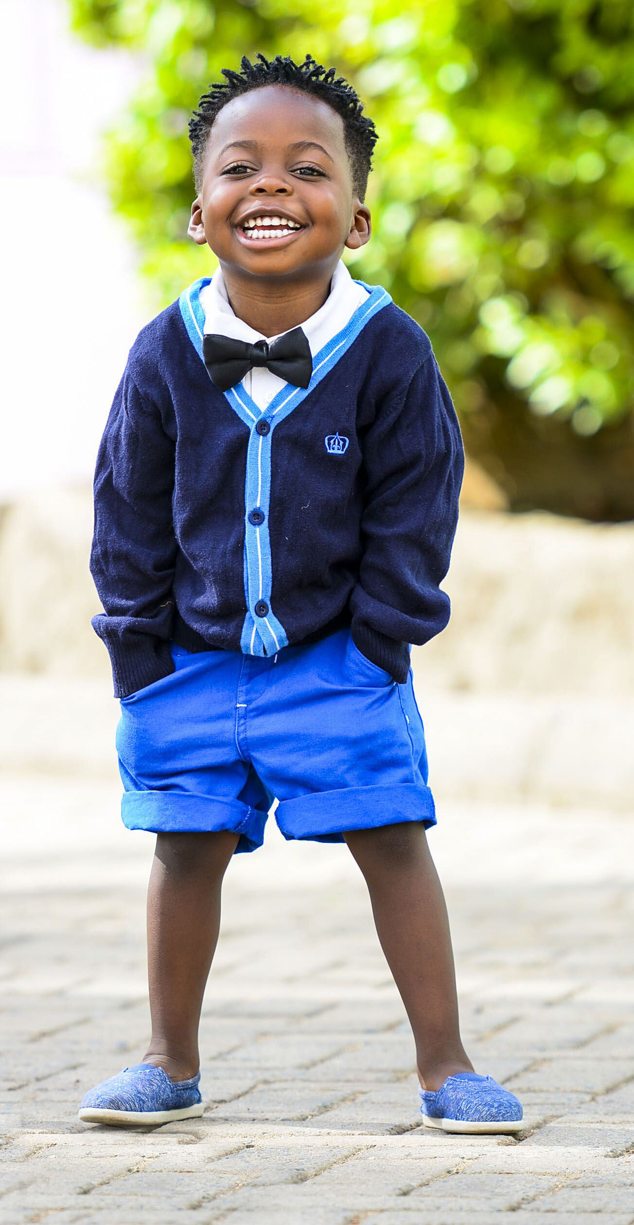 Preschool-age boy standing outside smiling, hands in pockets, wearing a bowtie, blue cardigan, blue shorts and shoes.