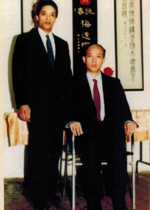 Grandmaster Moy Tung (left) with his Sifu, Grandmaster Moy Yat (seated).