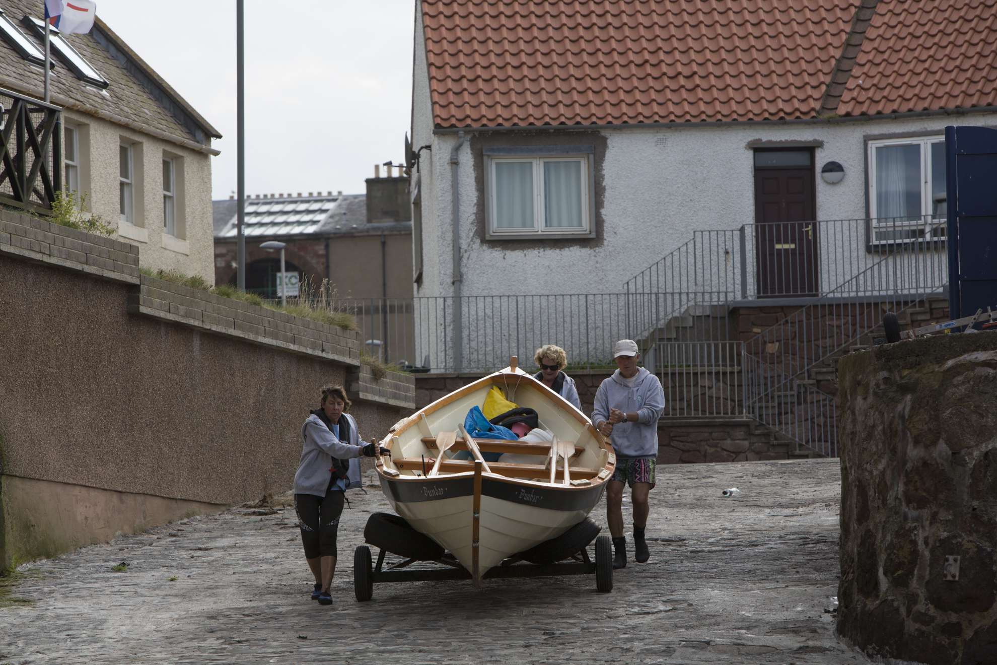 """From left, Diana Mackie, Pamela Maule and Kenny Maule wheel the """"Black Agnes"""" out to the water in Dunbar, Scotland."""