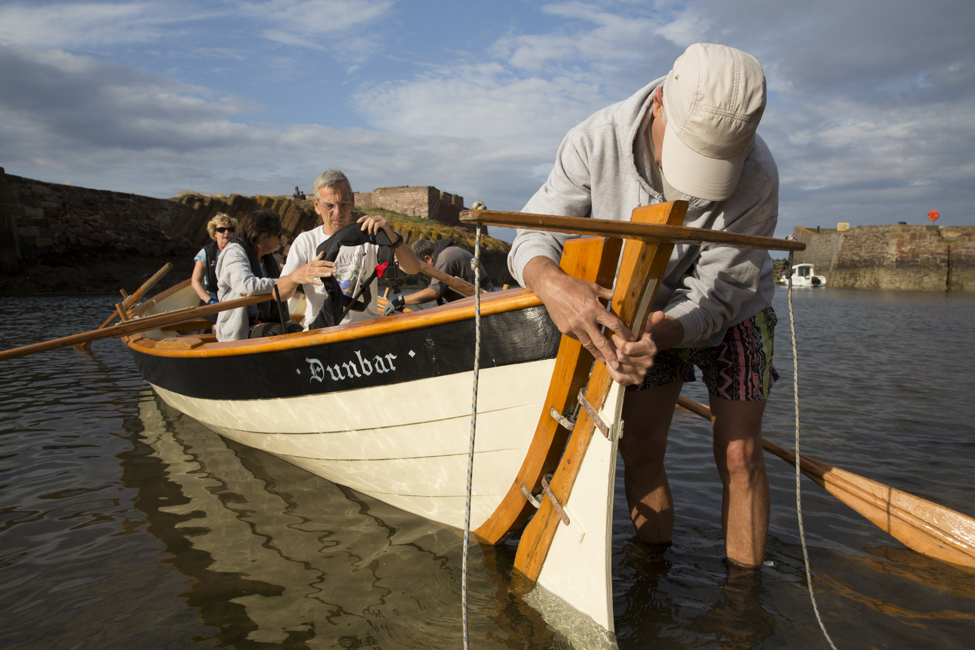 """Kenny Maule secures the rudder to the Dunbar Coastal Rowing Club's boat, """"Black Agnes"""", before coxing the boat."""