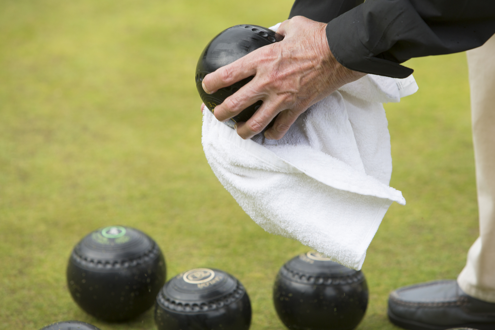 Janet Wright wipes raindrops off her bowls during a friendly ladies game of lawn bowling at Blackhall Bowling Club.