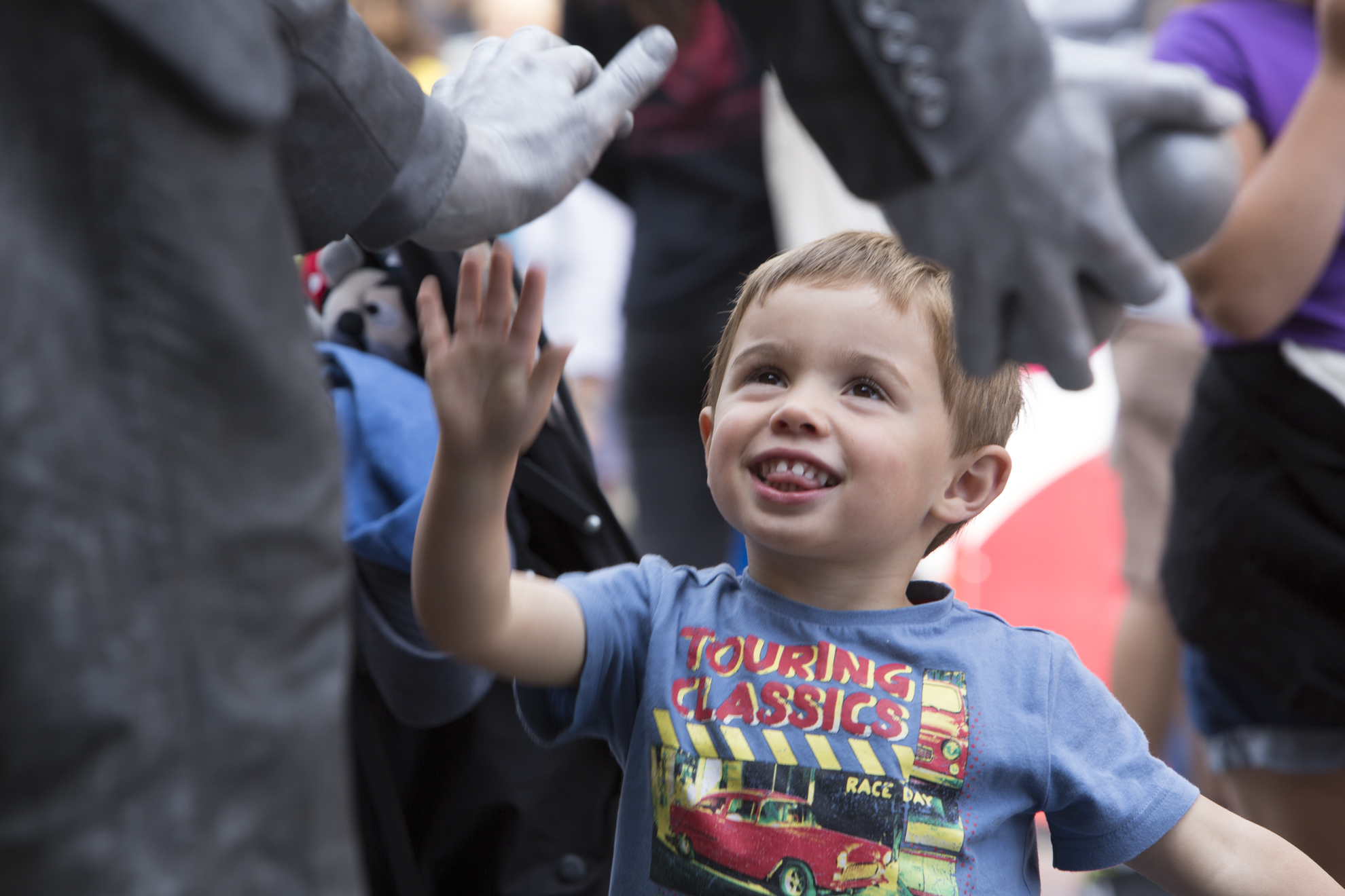Ollie Bathgate, 2, from Edinburgh, give a high five to John Godbolt in front of St. Giles Cathedral on the Royal Mile during the 2014 Edinburgh Festival of the Fringe in Edinburgh, Scotland.