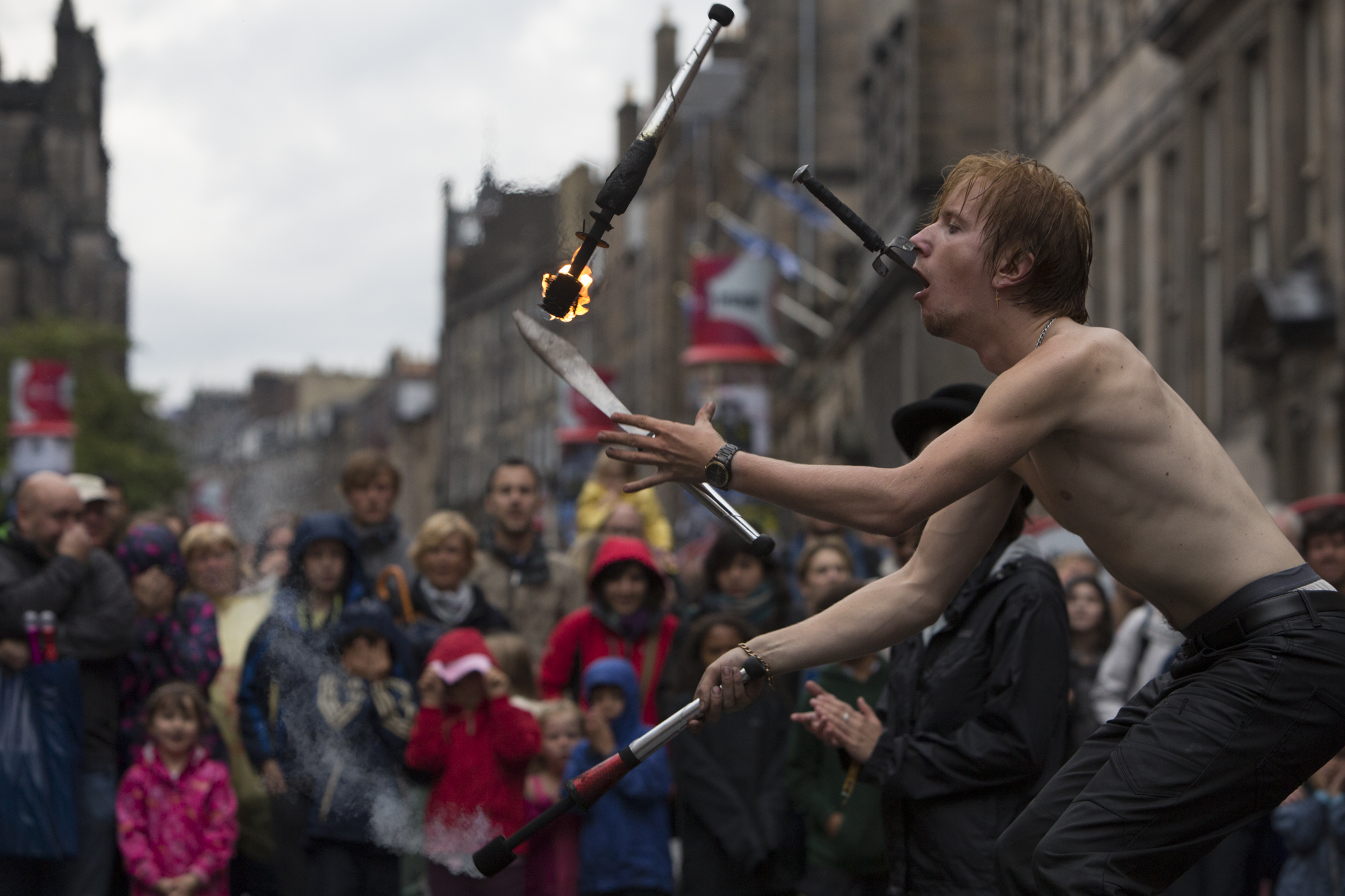Tommy Everson performs in front of a crowd in the rain during the 2014 Edinburgh Festival of the Fringe in Edinburgh, Scotland.