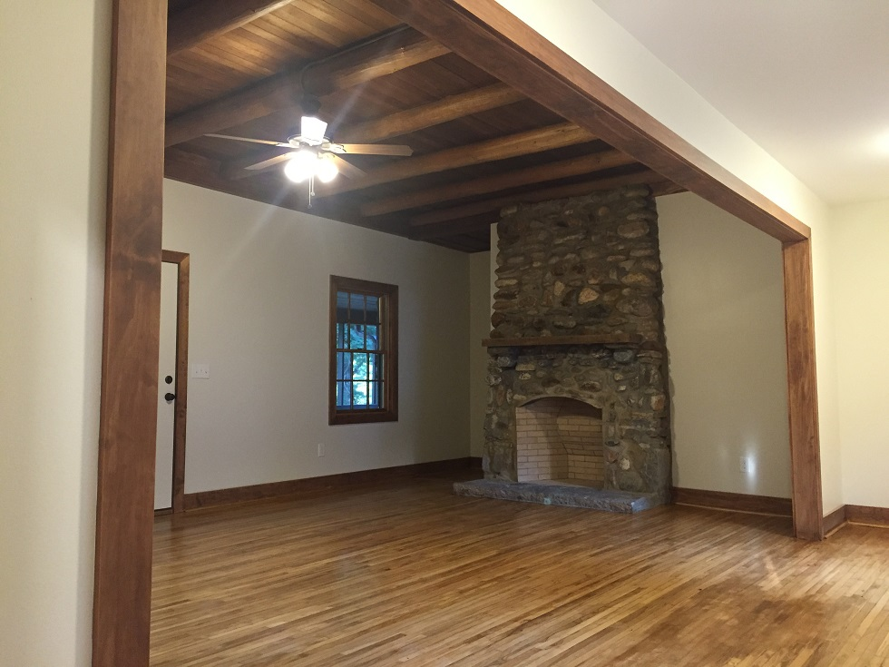 Great room with refurbished stone fireplace and exposed wood beams
