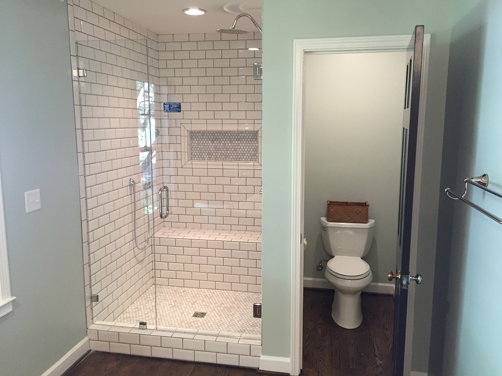 The master bath has a tile shower with a frameless glass door