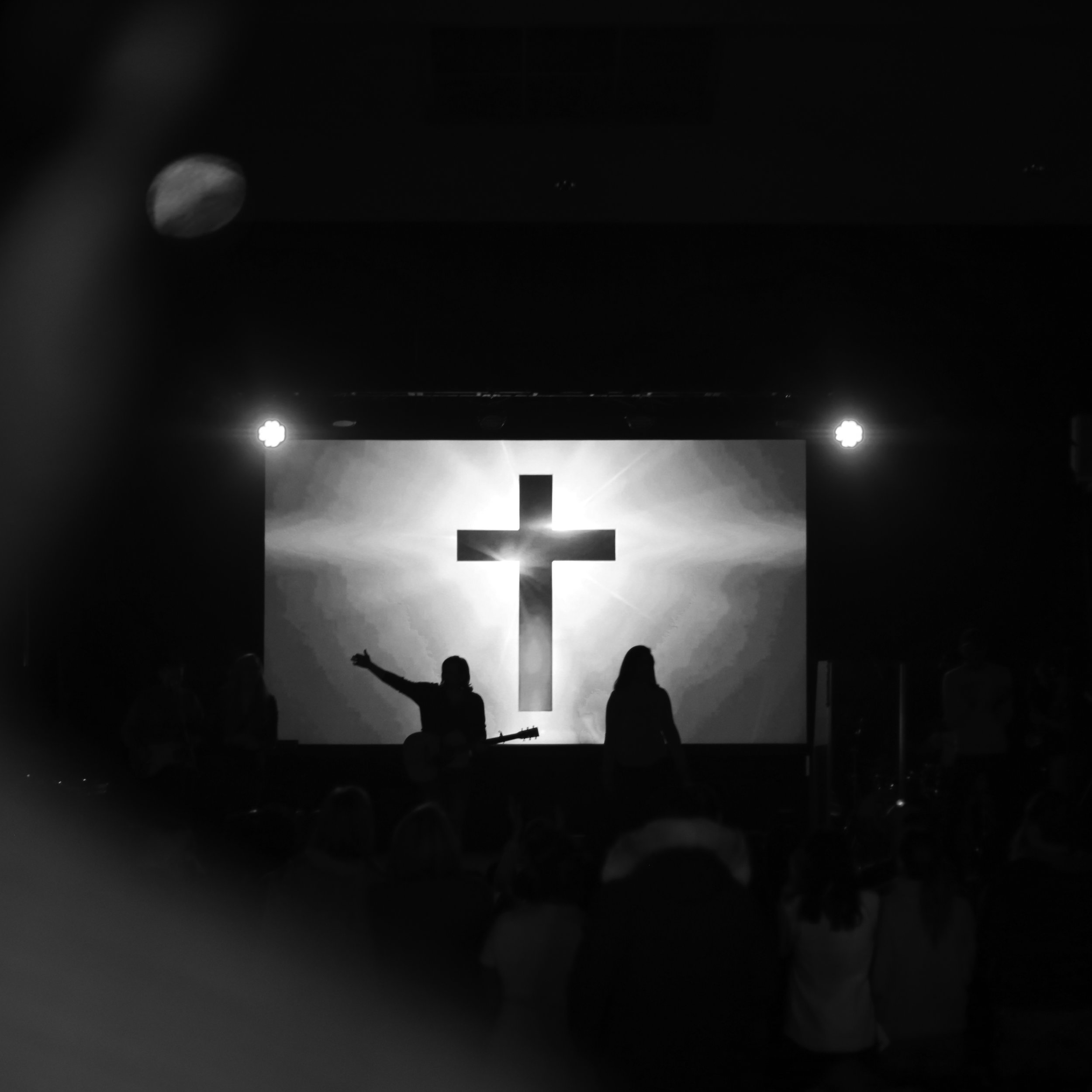 A cross is displayed on a projector in front of church members.