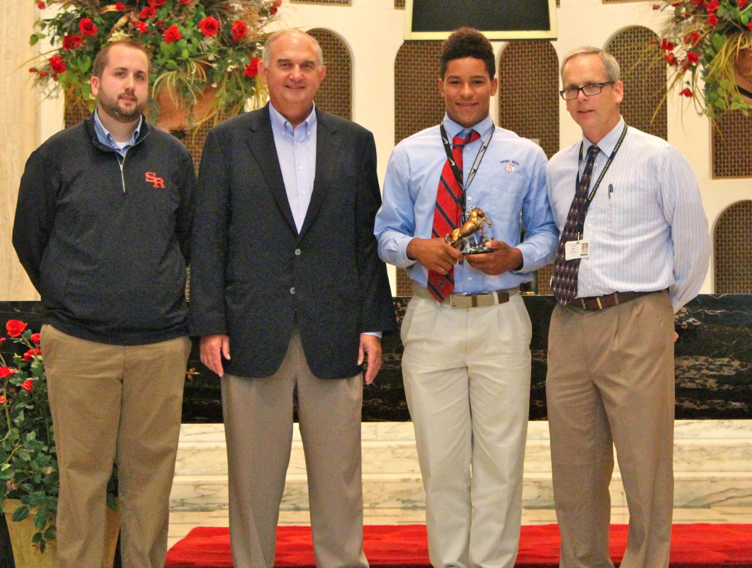 L to R: Josh Blaszak '04,Director of Student Life & Ministry; Ernie Mrozek '71, President;  Christopher Childers,Sophomore Mustang of the Month; Brendan Conroy, Principal