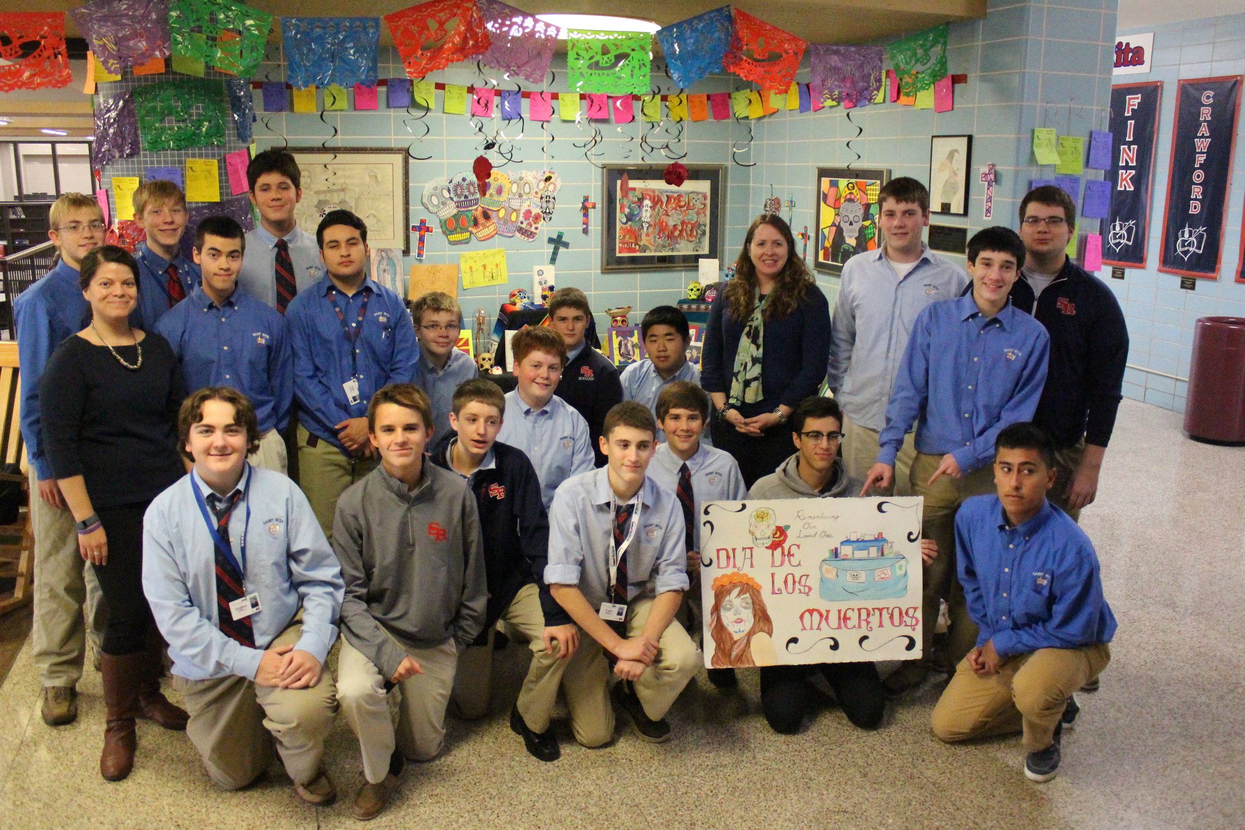 The St. Rita High School Spanish Club with Ms. Yanez and Mrs. Earley at the Day of the Dead altar