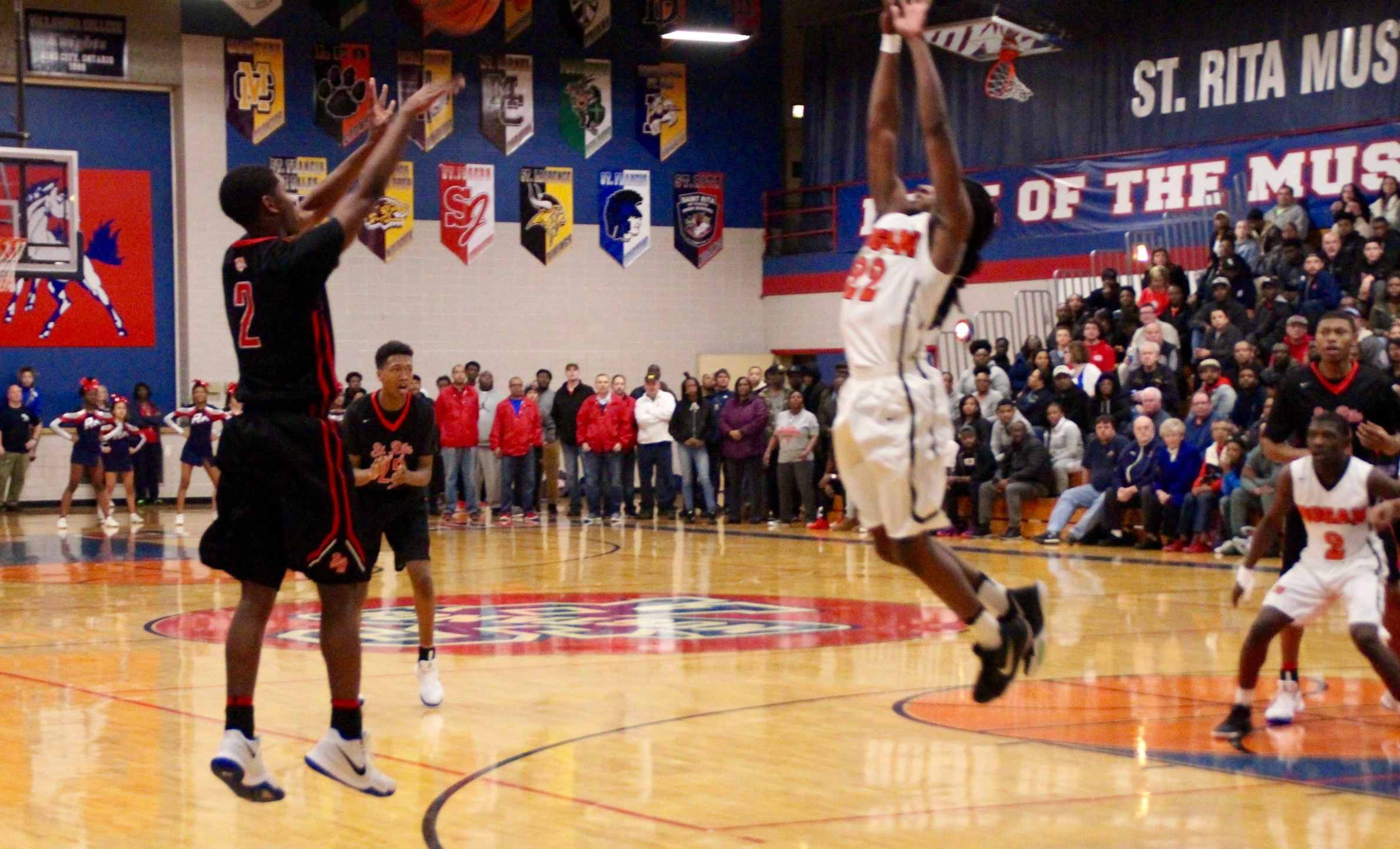 St. Rita's Rashaad Williams fires a three-point shot over a Bogan defender.