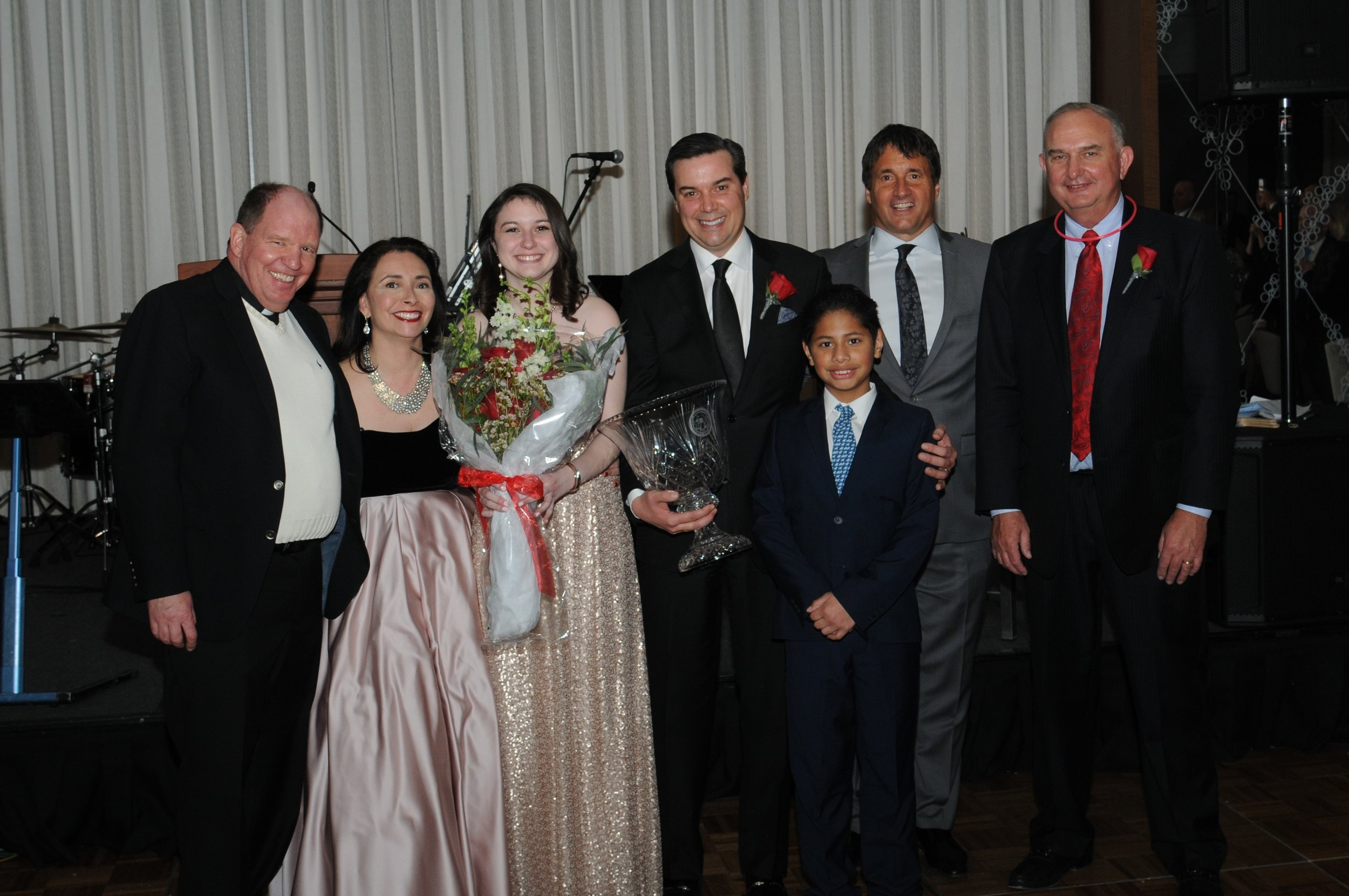 Couple of the Year Mark '90 and Mindy Hacker and family with Fr. Paul, Mike Zunica and Ernie Mrozek.