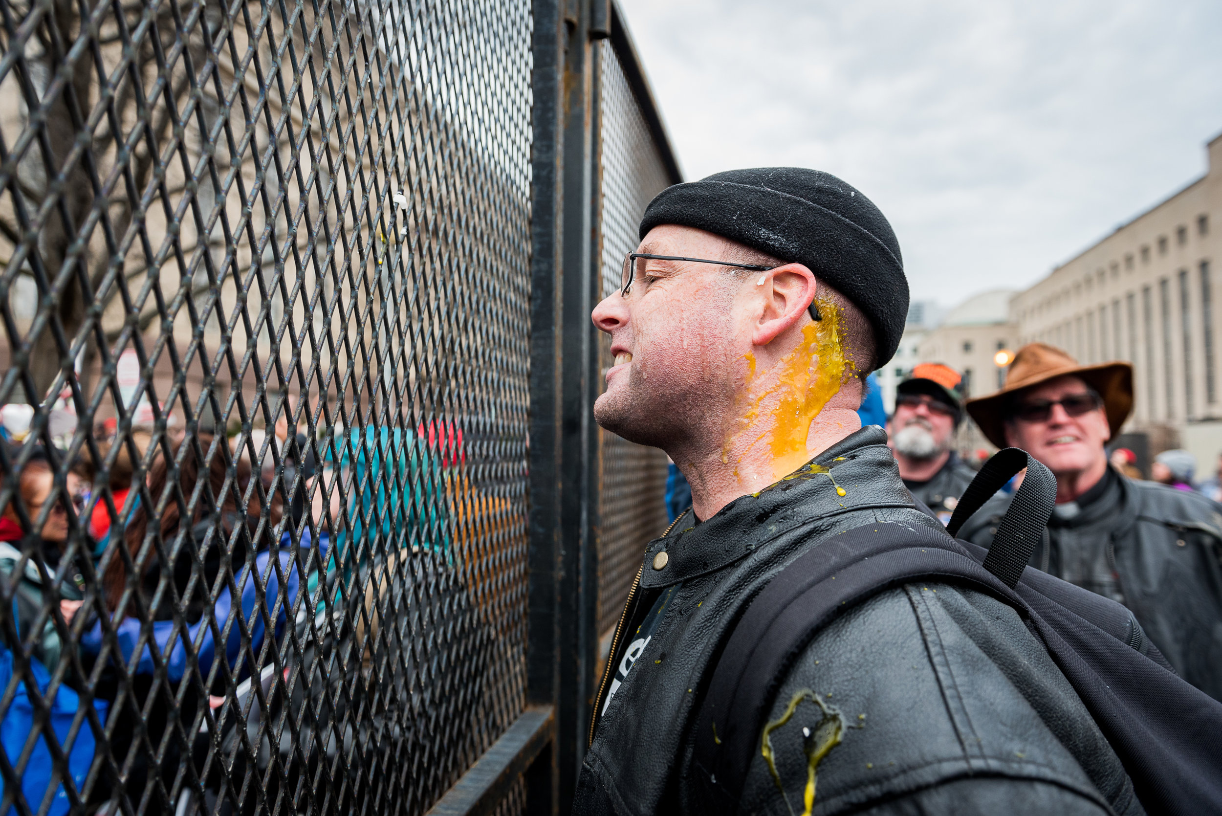 Washignton D.C. resident Chris Z., a member of Bikers For Trump, talks back at protesters through a security checkpoint barricade after being hit in the neck with an egg thrown by a protester, Friday, January 20, 2017.