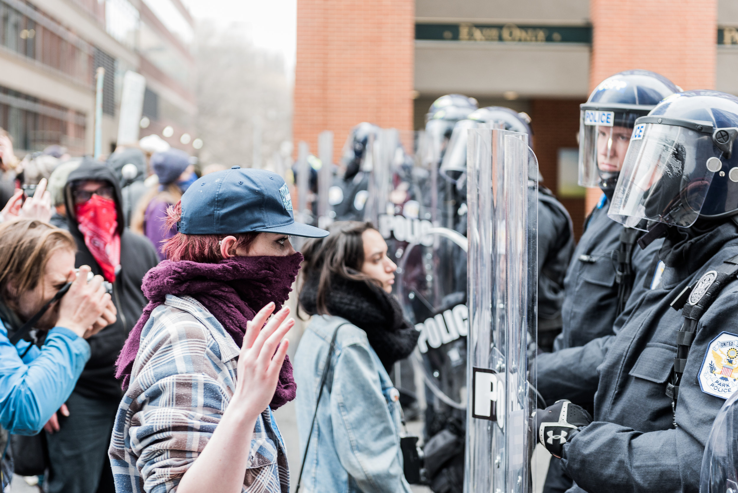A protester stares down a police officer in riot gear on 12th Street, Friday, January 20, 2017.