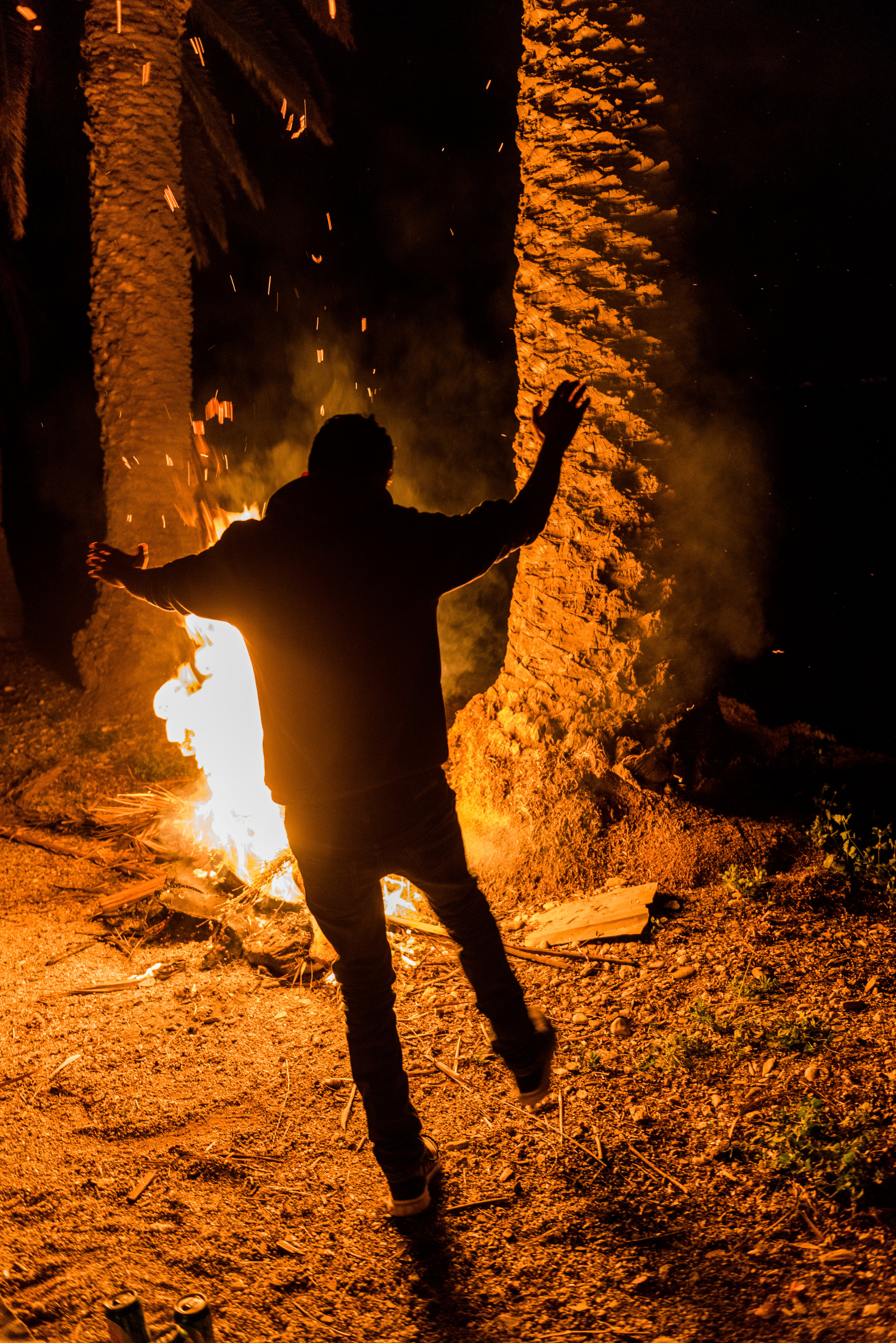 Aziz dances to the music in front of the roaring palm tree branch fire.