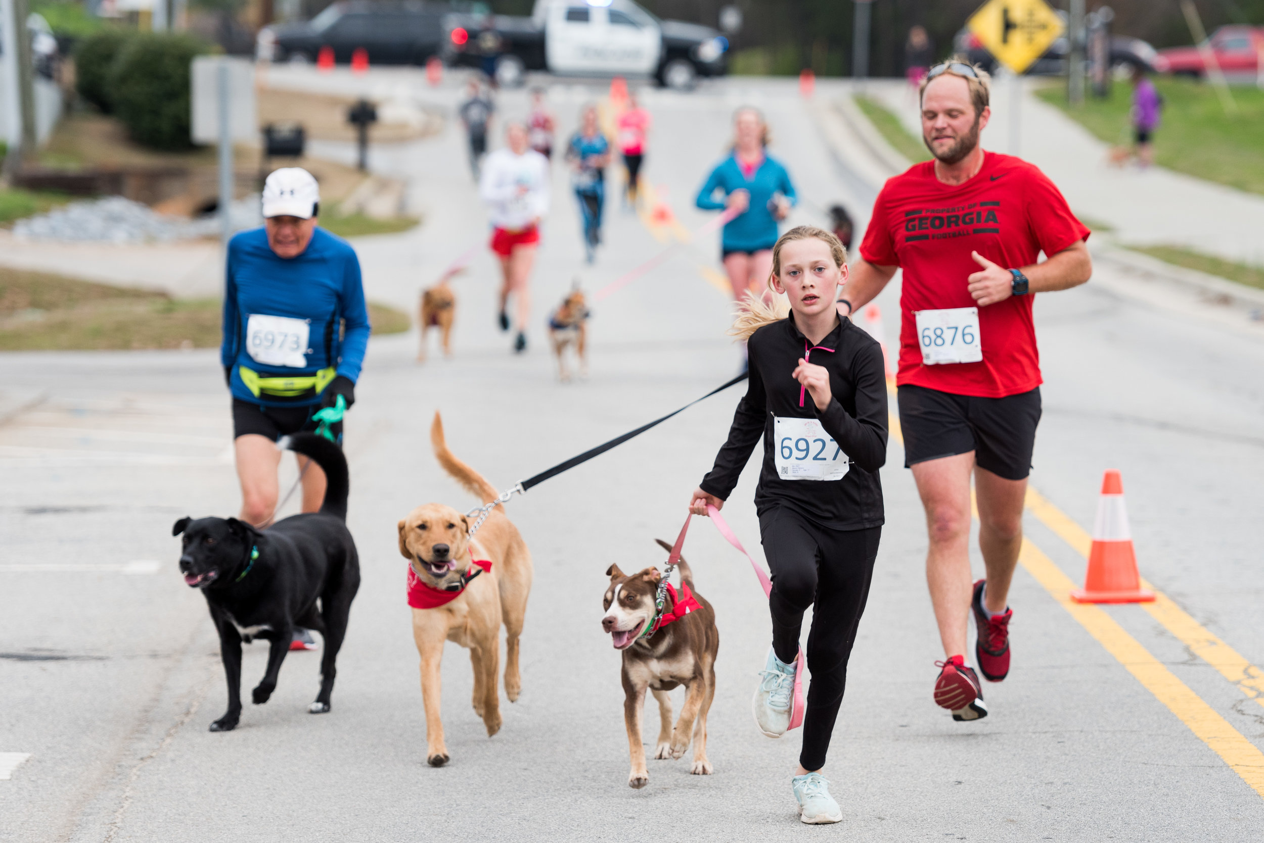 Maren Hanson, 11, runs for the finish line with George Daigh of Maysville (red) as part of the Farm to 5k challenge at the Run for the Rescues 5k on March 24 in Suwanee.