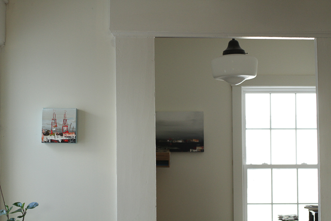 Looking back into the office, from the kitchen. We have several paintings by the lovely  Sarah Jones , and I just love them. Give me off-white walls, wood floors, plenty of plants and some great art, and I am in raptures.