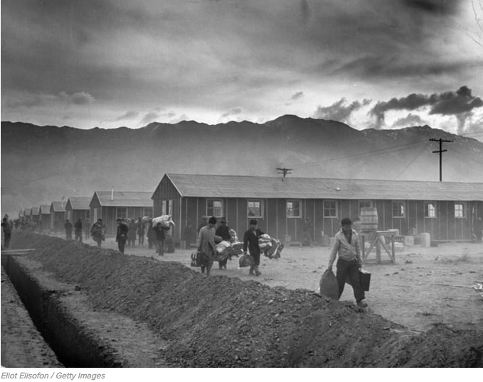 A group of Japanese-Americans arrive at the Manzanar incarceration camp carrying their belongings in 1942.