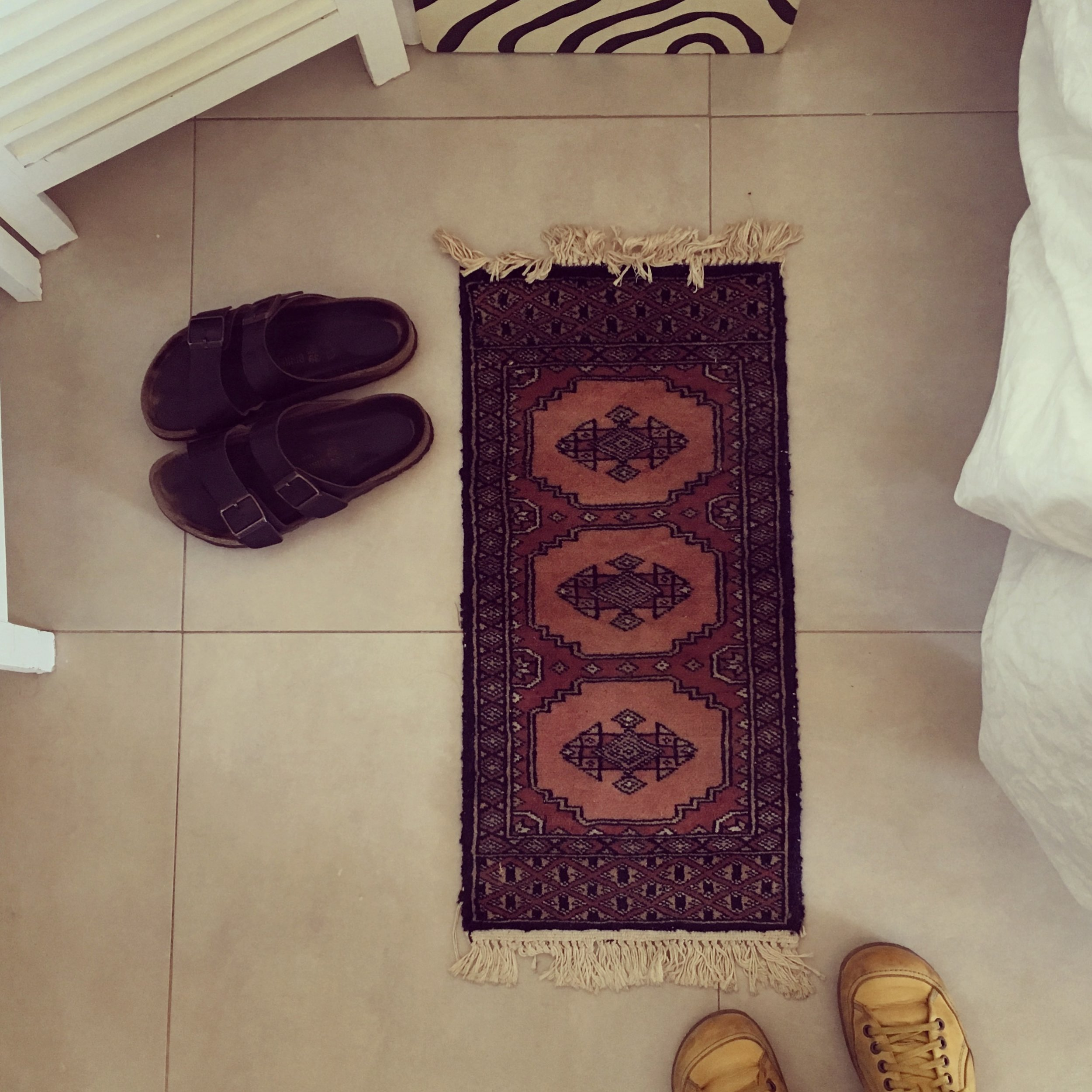 The rug, my sandals, and me in my travelling shoes across from the water in Sitges, Spain.