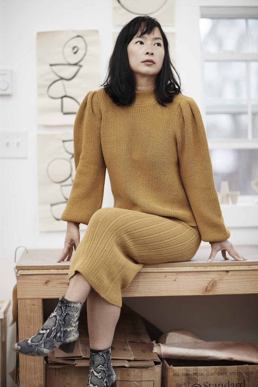 RJ wears   Mia sweater   +   Ava skirt   in Mustard
