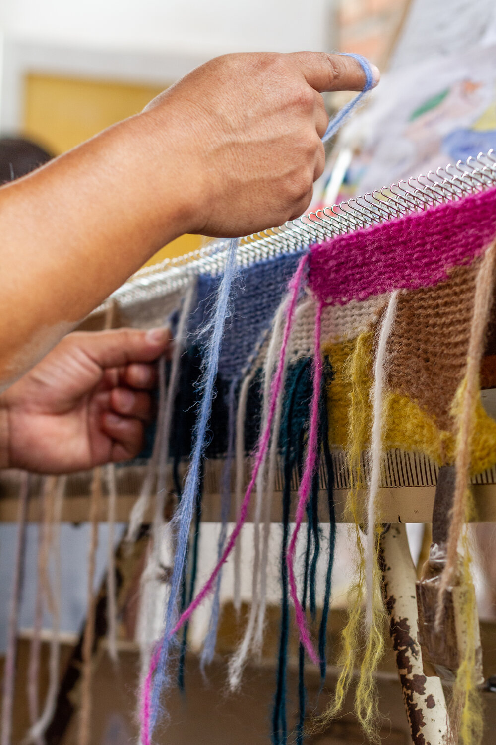 Yarn is hand-laid in across the machine needles to build and create the shapes of the pattern within the knitting.
