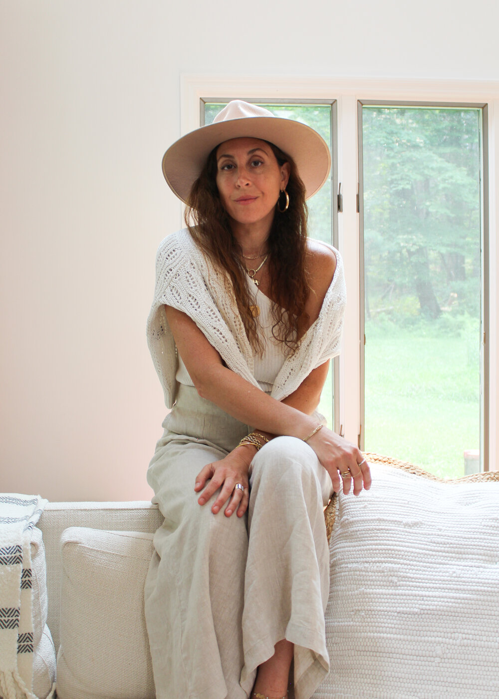 Jenny wears Karla one-shoulder top   (SHOP)   w/ Pandora Sweater   (SHOP)   layered back to her own linen pant. Our Madras home throw is layered over the couch.