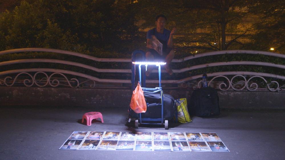Zeng Xian Fang working at night on the pedestrian bridge in Xiaobeilu