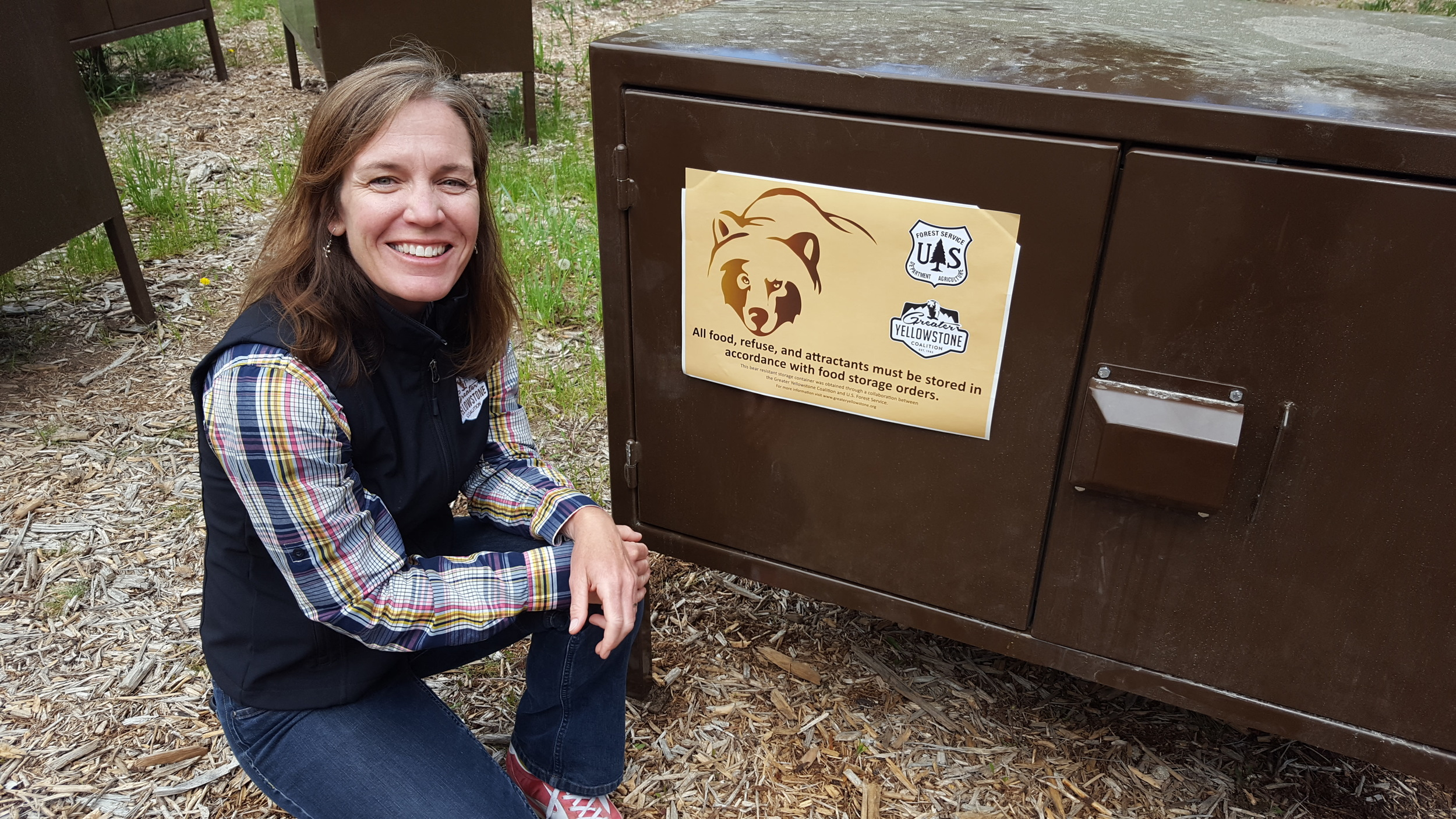 Greater Yellowstone Coalition's Kathy Rinaldi with one of the bear boxes GYC and the Boy Scouts paid for to keep people safe and bears wild at Treasure Mountain Scout Camp. The 75-acre camp has attracted its share of bears in the past few years; GYC and the Scouts are working to end the conflict in Teton Canyon. (Photo Greater Yellowstone Coalition.)