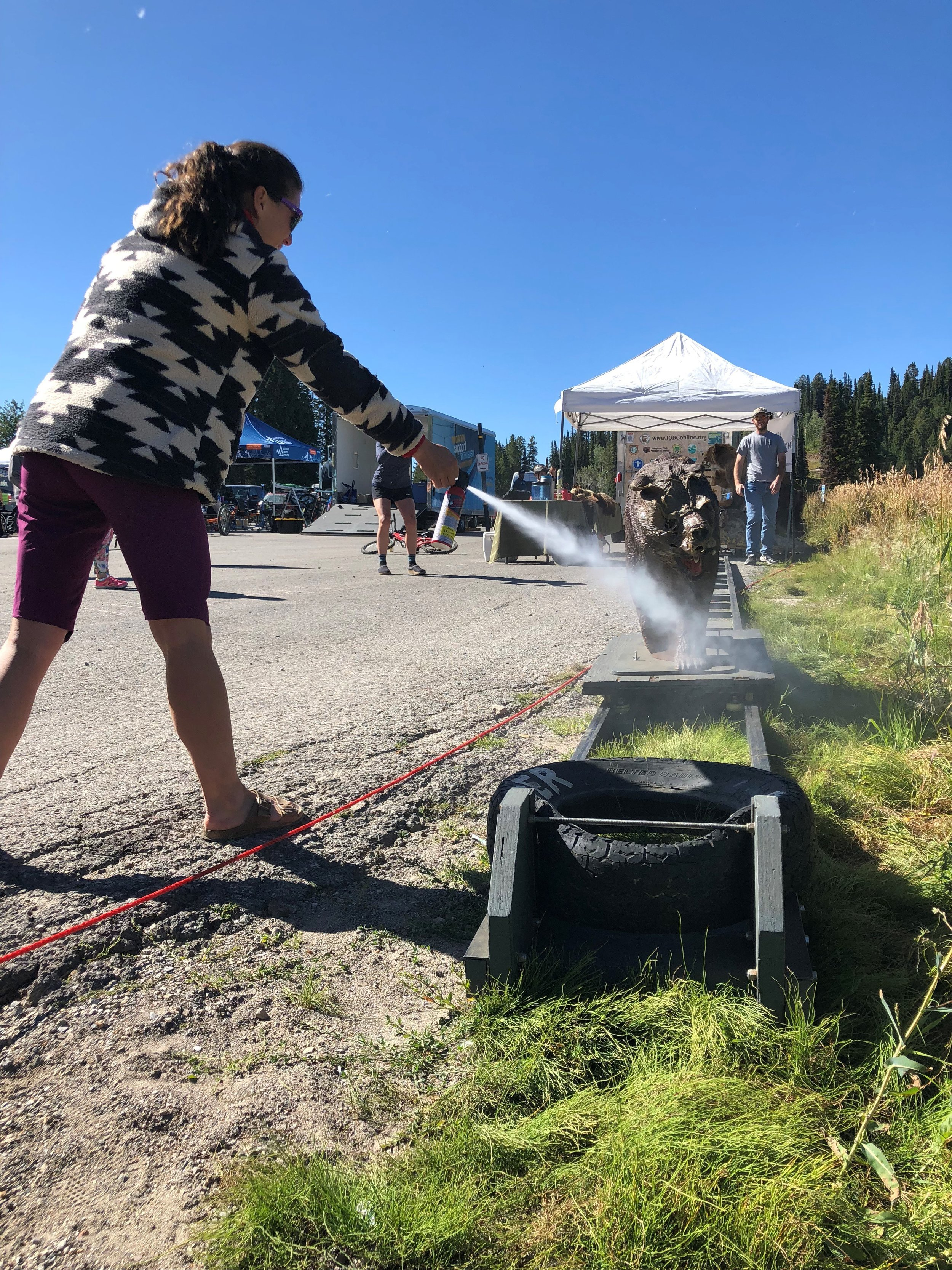 A participant uses inert bear spray to test her reflexes with the Charger, the mechanical charging bear we brought to a mountain biking festival in Teton Valley, Idaho. (Photo GYC.)