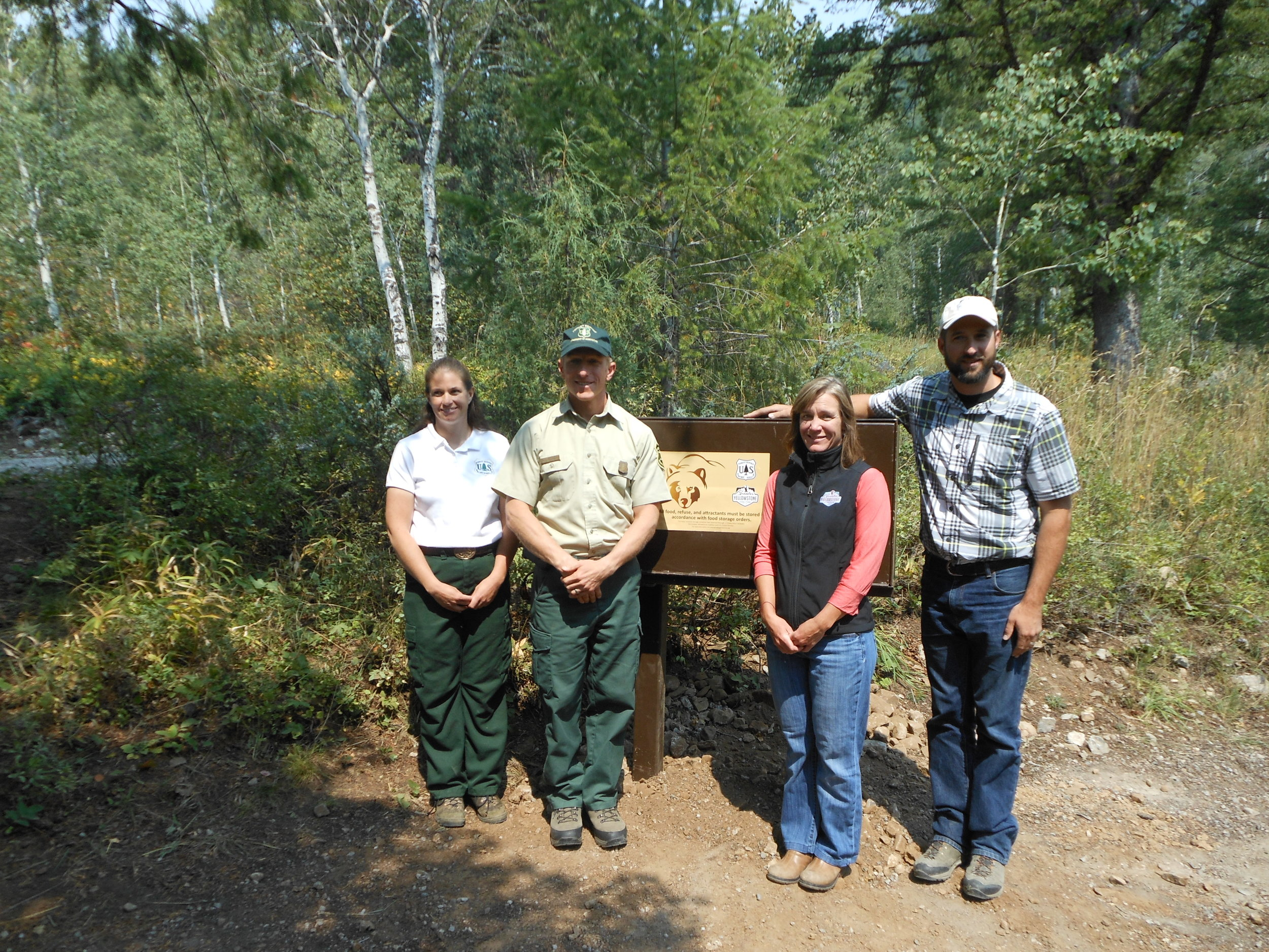 Idaho Conservation Coordinator Kathy Rinaldi (2nd from right), Wildlife Program Coordinator Chris Colligan (far right), and two Forest Service employees with a recently installed food storage container at a campground near Palisades, Idaho. (Photo GYC.)