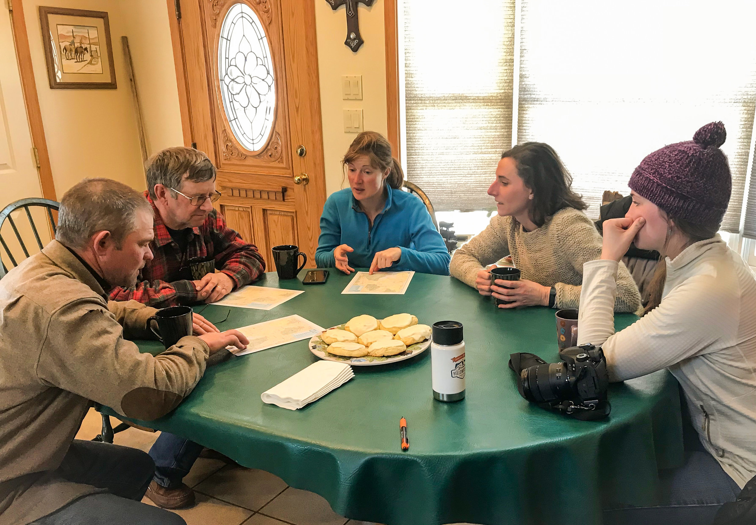 (L to R) Herdsman Andy Peterson, ranch owner John Anderson, herdswoman Amber Mason, GYC's Darcie Warden, and GYC's Brooke Shifrin sit around John's table and locate the cattle grazing allotment on a map.  (Photo GYC/Emmy Reed.)