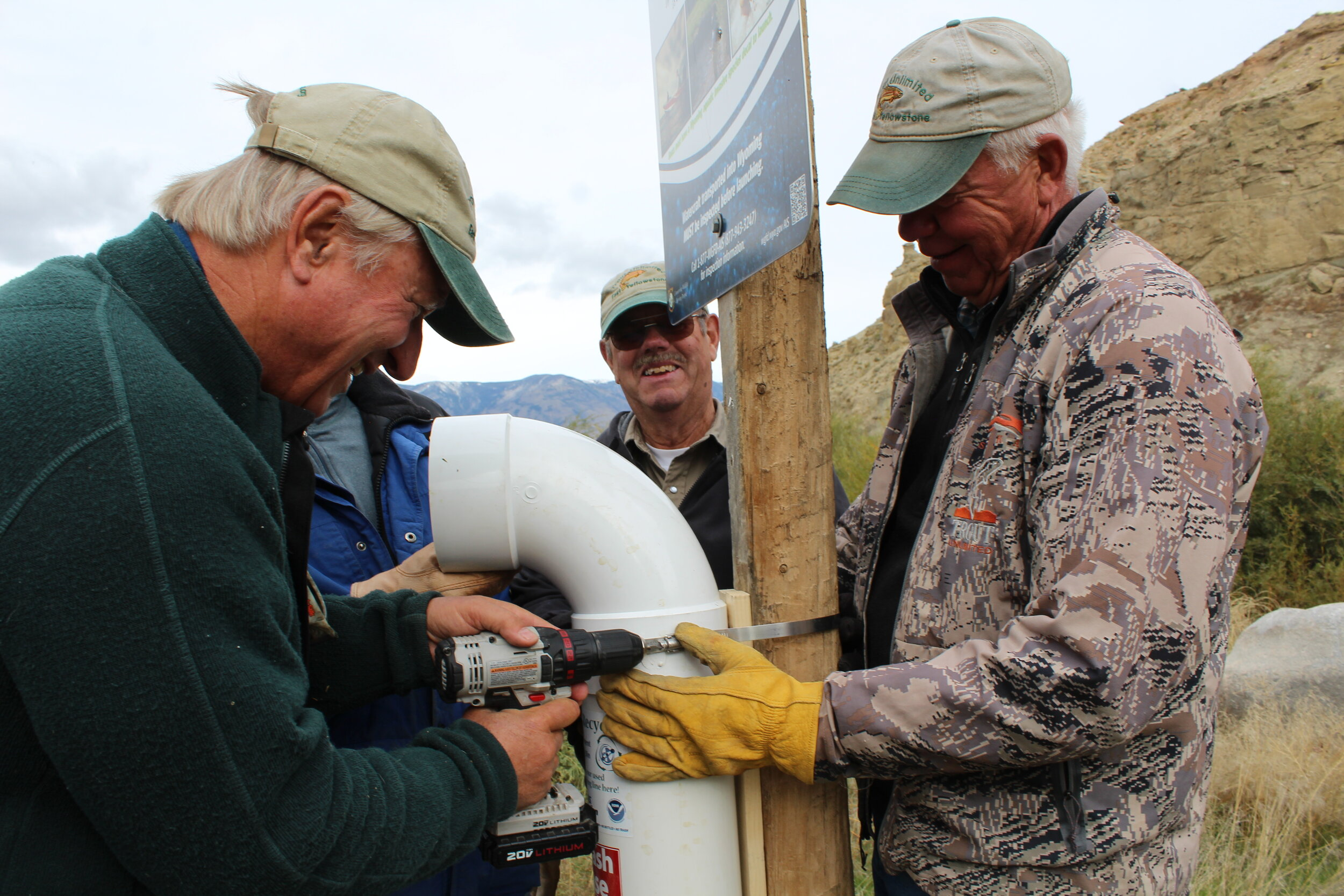 Volunteers install a  microfilament recycle station, which allows for people to properly dispose of used fishing line.  (Photo GYC/Emily Reed.)