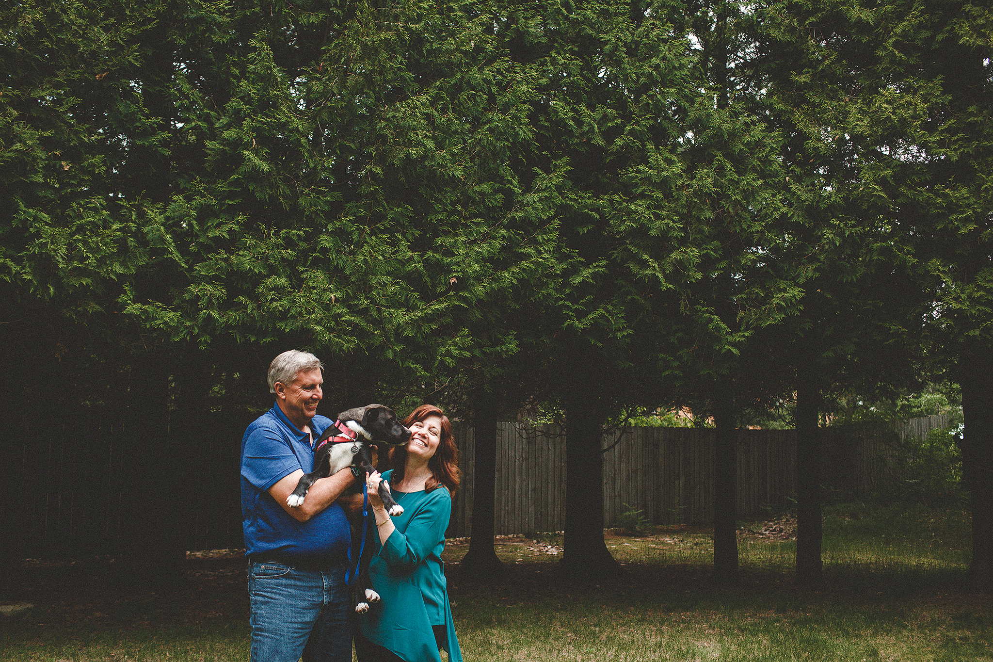 Mature couple laughing & holding dog in the forest | Sheboygan, WI photographer | Chrissy Deming photography